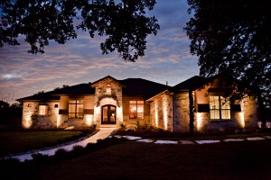 Custom home with porch lights on during the evening.